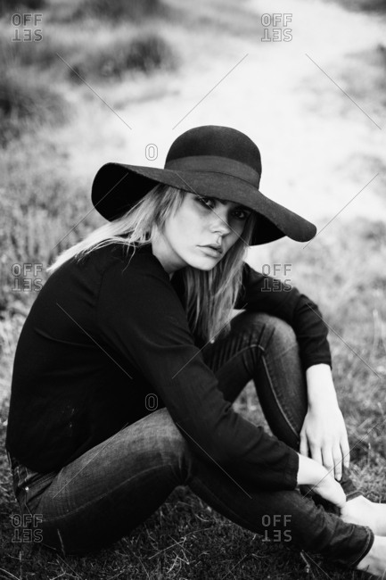 Portrait of young woman wearing black hat sitting on a meadow