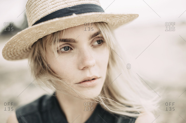 Portrait of daydreaming young woman wearing straw hat in nature