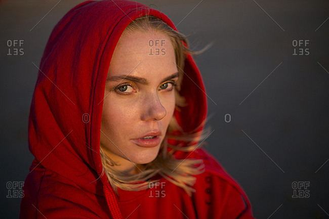 Portrait of young woman wearing red hooded jacket in evening light