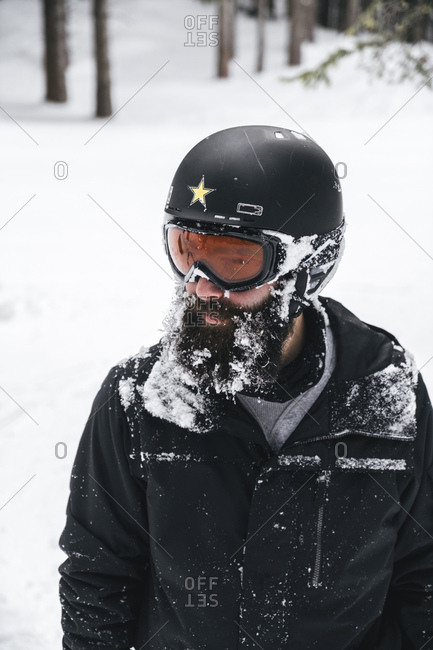 Snow-covered young man in skiwear looking sideways