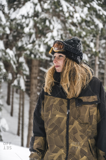 Young woman in skiwear in winter forest looking sideways