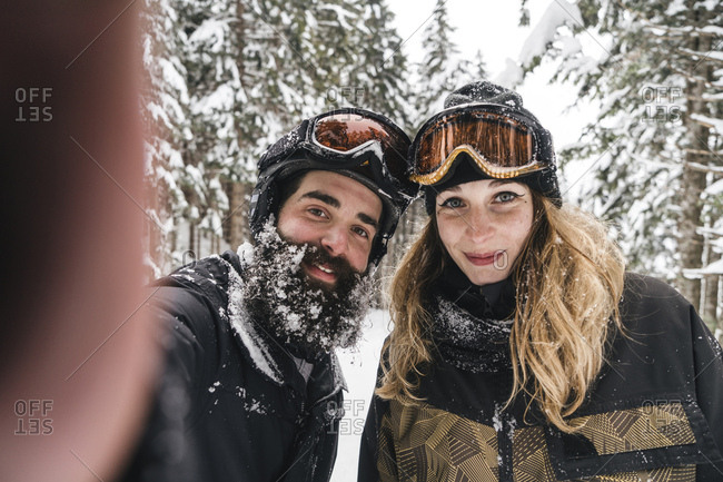 Selfie of smiling couple in skiwear in winter forest