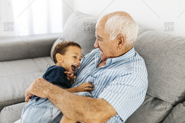 Grandson and grandfather laughing while tickling each other on the couch