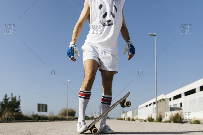 Man in stylish sportive outfit standing on skateboard upside down against blue sky