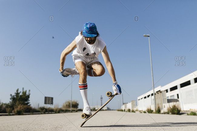 Man in stylish sportive outfit standing on skateboard against blue sky