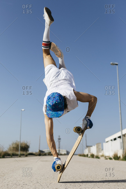 Back view of man in stylish sportive outfit standing on skateboard upside down against blue sky