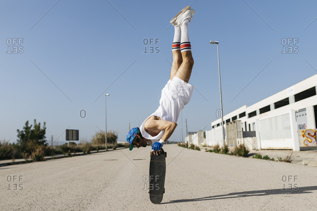 Man in stylish sportive outfit standing on skateboard upside down