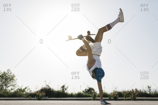 Side view of sportive man doing exciting trick with skateboard flipping on one hand on street