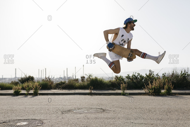 Sportive man jumping above ground with skateboard on hands