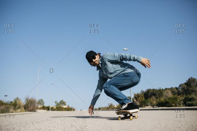 Trendy man in denim and cap skateboarding