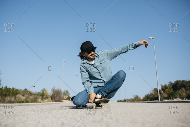 Trendy man in denim and cap skateboarding