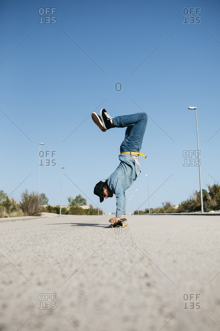 Trendy man in denim and cap skateboarding- standing on skateboard upside down