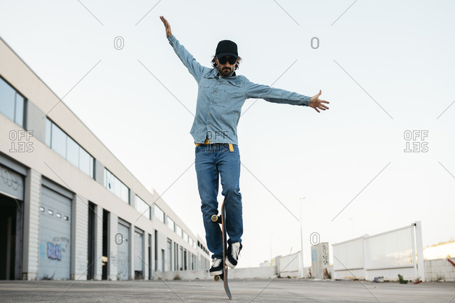 Trendy man in denim and cap skateboarding- standing on skateboard