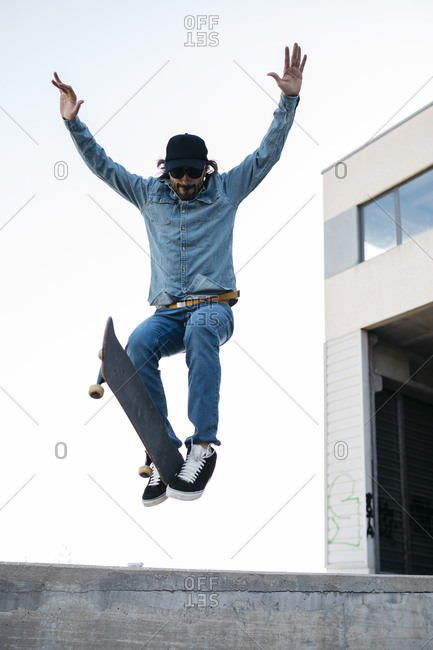 Trendy man in denim and cap skateboarding- doing jump with skateboard from concrete ramp