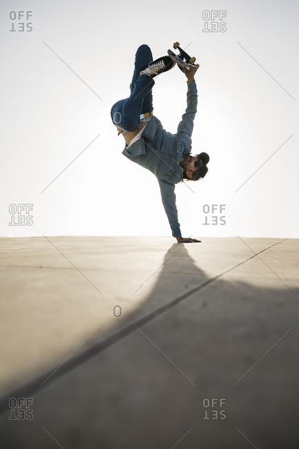 Stylish man in denim outfit showing trick with skate in handstand