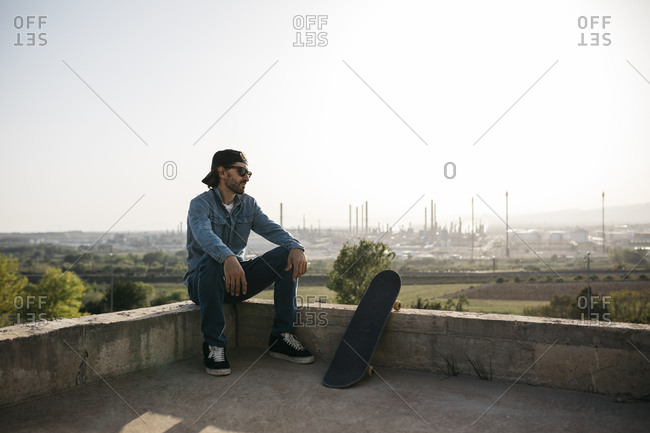 Skateboarder dressed in casual clothes resting at sunset