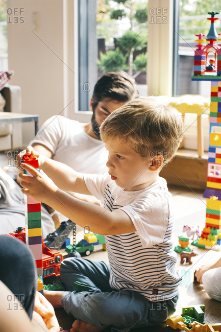 Boy with his family stacking building blocks on the floor