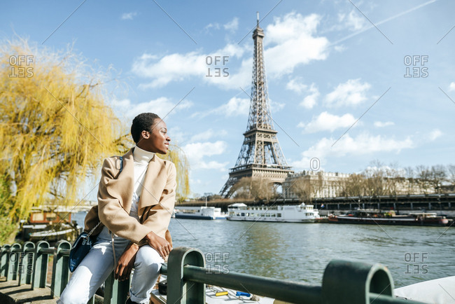 France- Paris- Smiling woman at river Seine with the Eiffel Tower in the background