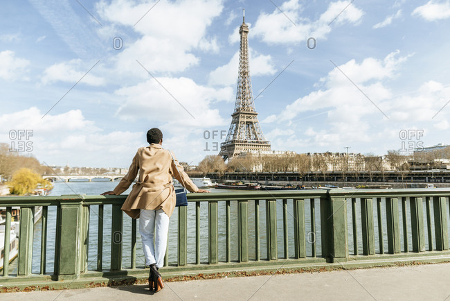 France- Paris- Female tourist looking towards the Eiffel tower and the Seine river