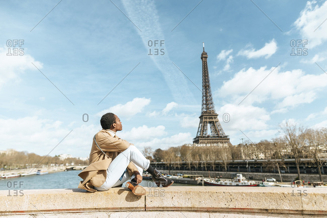 France- Paris- Woman sitting on bridge over the river Seine looking at Eiffel tower