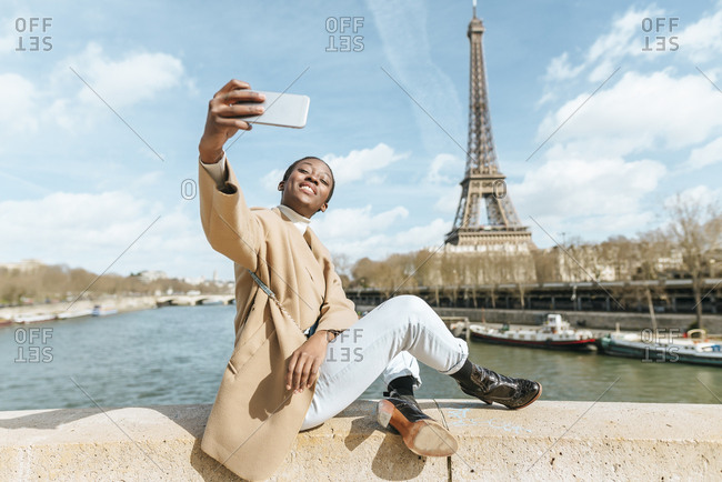 France- Paris- Woman sitting on bridge over the river Seine with the Eiffel tower in the background taking a selfie