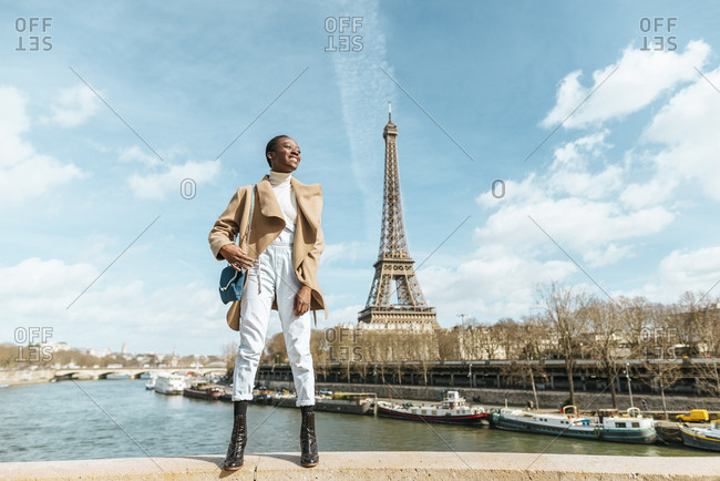 France- Paris- Smiling woman standing on a bridge with the Eiffel tower in the background