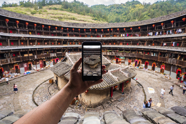 China- Fujian Province- hand taking cell phone picture of the inner courtyard of a tulou in a Hakka village