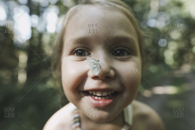 Portrait of smiling little girl with butterfly on her nose