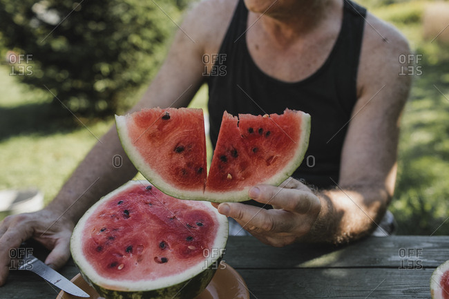Senior man's hand holding watermelon slice