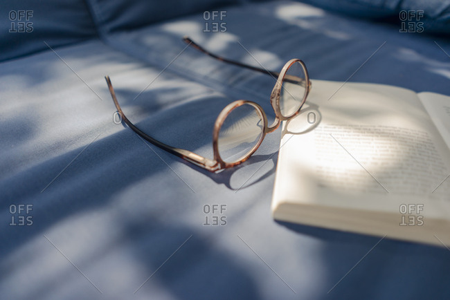 Eyeglasses and book lying on couch