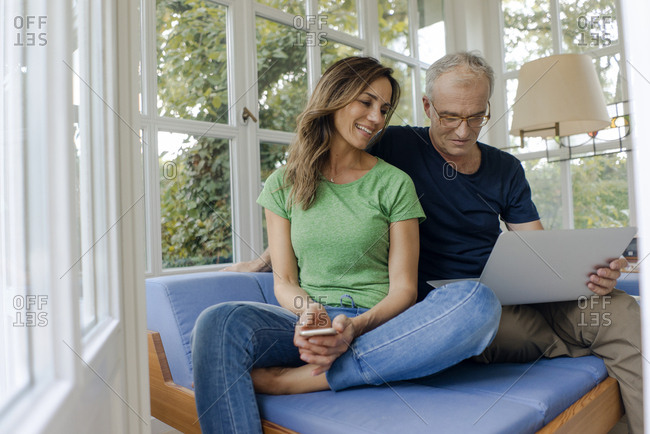Smiling mature couple sitting on couch at home sharing laptop