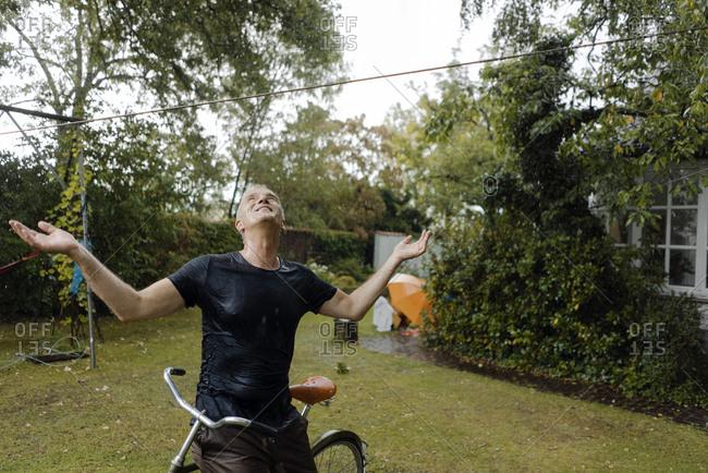 Mature man with bicycle enjoying summer rain in garden