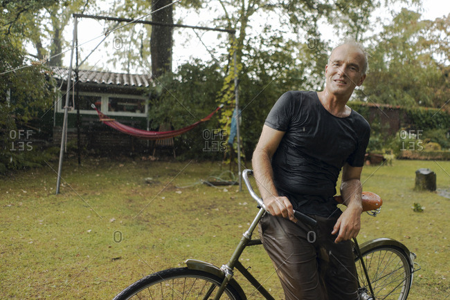 Portrait of mature man with bicycle in summer rain in garden