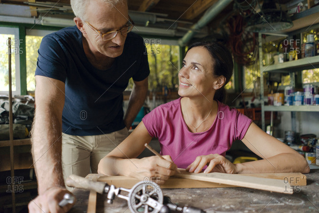 Smiling mature man watching woman working in workshop