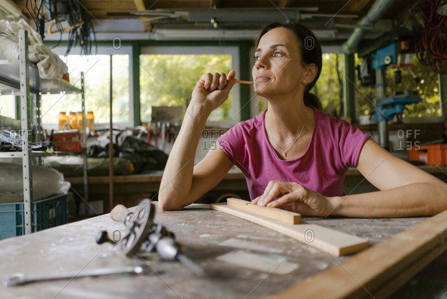 Mature woman at workbench in her workshop thinking