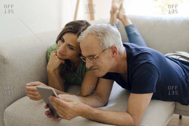 Smiling mature couple lying on couch at home sharing tablet