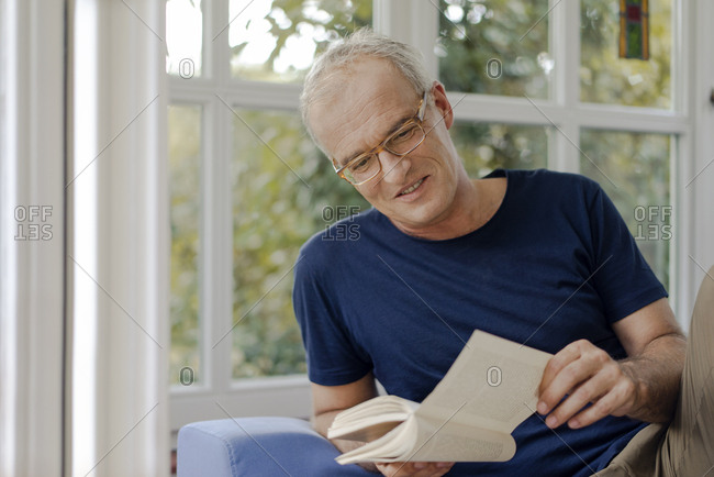 Smiling mature man at home reading book