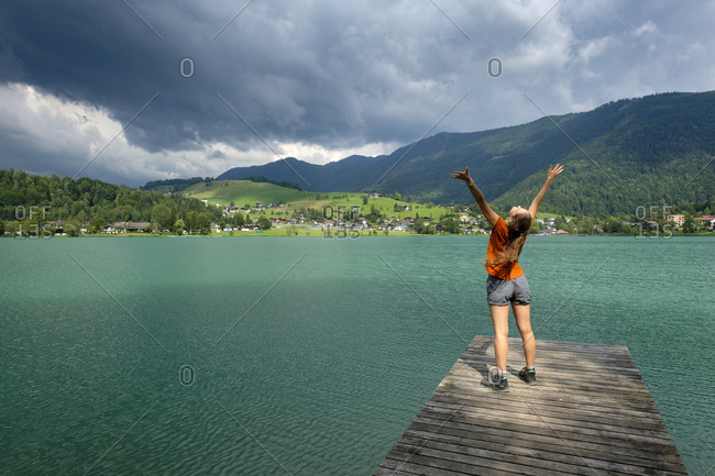 Teenager standing on wooden jetty- raised arms