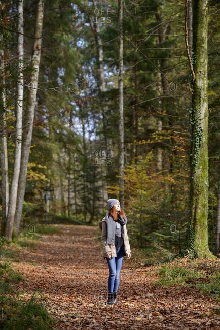 Redheaded teenage girl enjoying autumnal forest