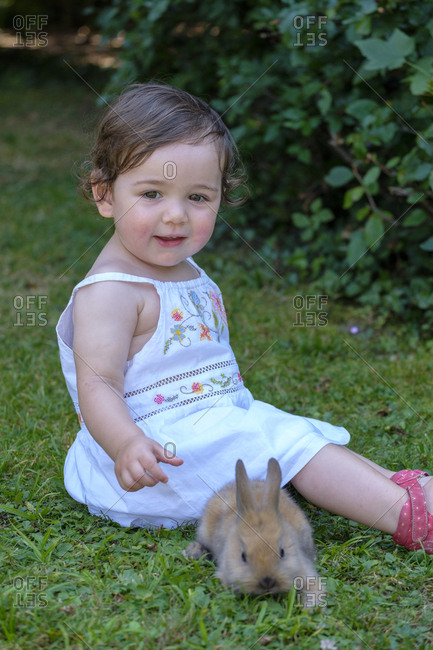 Portrait of content baby girl sitting on a meadow with young bunny