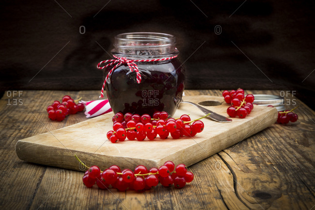 Jam jar of currant jelly and red currants on wooden board