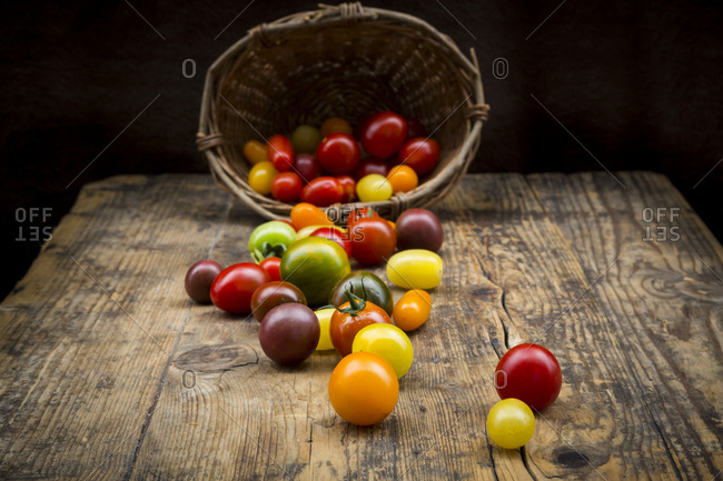 Basket of Heirloom tomatoes on wood