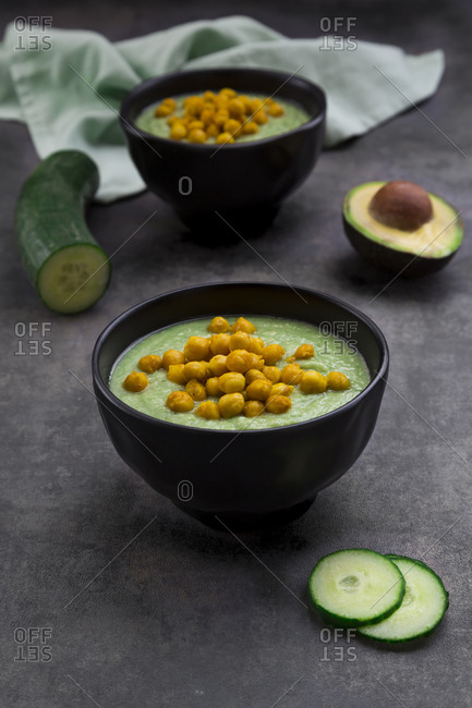 Bowl of green gazpacho with avocado and curcuma roasted chick peas