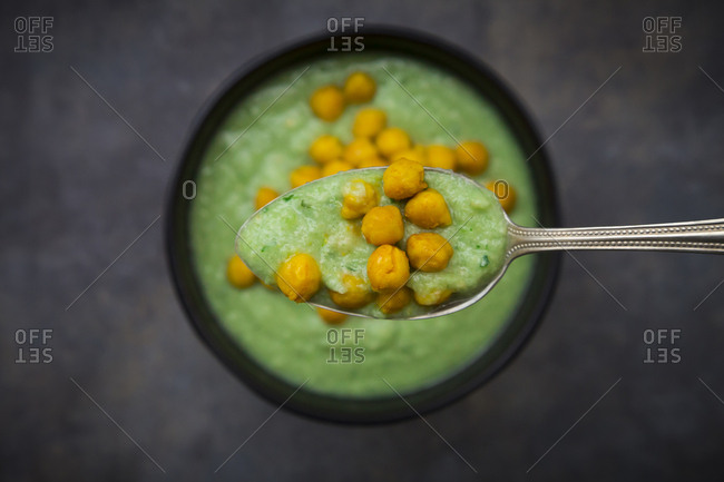 Bowl of green gazpacho with avocado and curcuma roasted chick peas- on spoon- close-up