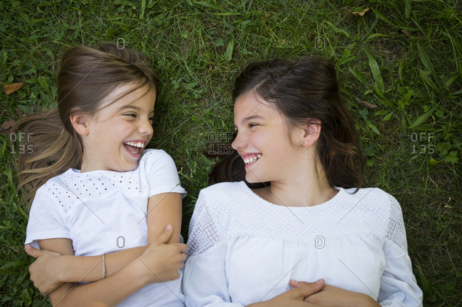 Two sisters lying together on a meadow having fun