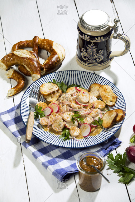Bavarian veal sausage salad with roasted pretzel rolls- sweet mustard- pretzels- red radish and beer mug