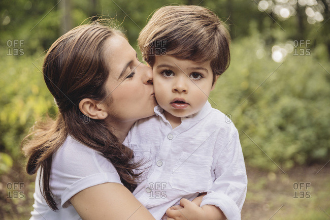 Mother kissing toddler on cheek in park
