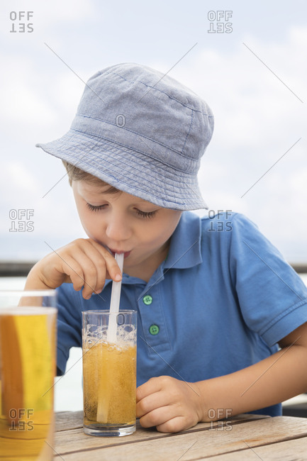 Boy blowing bubbles with straw in his soft drink