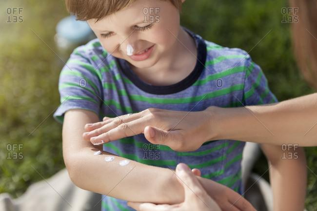 Mother applying sun cream on son's arm