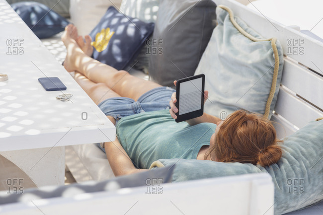 Young woman reading e-book- lying on bench